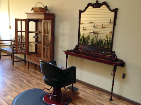 Organic Salon Project Cutting Station Chair, Antique Mirror, and wooden cabinet display.